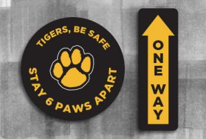"Image shows a circular graphic with text ""Stay 6 Paws apart"" with a tiger paw in the center. Second graphic is rectangular with an arrow and text ""one way""."