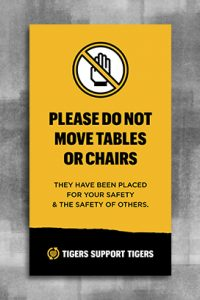 "Black text on gold background reads ""Please do not move tables or chairs. They have been placed for your safety and the safety of others"". At the bottom is a black page tear with the words ""Tigers Support Tigers"" and the University of Missouri logo to the left with a white outlined shield, gold MU and the text ""University of Missouri""."