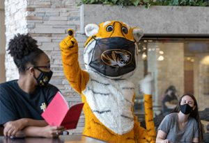 Photo of Mizzou Mascot Truman the Tiger wearing a face mask with two students also wearing face masks.