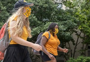 Photo of two Mizzou students wearing face masks outside while walking 6 feet apart.