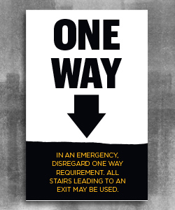 "Text ""One Way"" with Large black arrow pointing down and a black page tear at the bottom with gold text ""disregard in an emergency. All stairs leading to an exit may be used."""