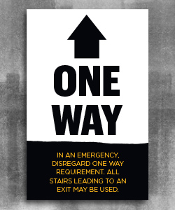"Large black arrow pointing up with text ""One Way"" beneath and a black page tear at the bottom with gold text ""disregard in an emergency. All stairs leading to an exit may be used."""